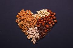 Zusammenstellung von Nüssen auf einem schwarzen Hintergrund - gesunder Snack Herz von Nüssen Stockbilder