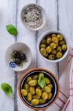 Zusammenstellung von Oliven mit Kraut und Seesalz auf weißer hölzerner Rückseite lizenzfreies stockfoto