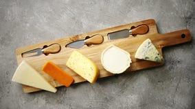 Zusammenstellung von verschiedenen Arten von den Käsen gedient auf hölzernem Brett mit Gabel und Messern stock video
