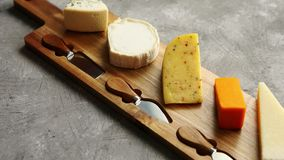 Zusammenstellung von verschiedenen Arten von den Käsen gedient auf hölzernem Brett mit Gabel und Messern stock footage