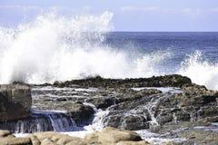 Zusammenstoßendes Wellen-und Fließenwasser auf Küstenfelsen, Uvongo, Südafrika lizenzfreies stockfoto