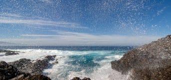 Zusammenstoßende Wellen, die über den Felsen spritzen lizenzfreies stockfoto