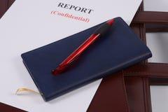Roter Stift und blaues Notizbuch Stockbilder