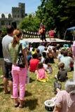 Zuschauer, die auf Gras-Uhr-Magier Perform At Festival sitzen Lizenzfreie Stockfotografie