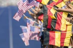 Zuschauer, die Flaggen Deutschland USA wellenartig bewegen Lizenzfreies Stockbild