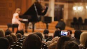 Zuschauer im Konzertsaal während der Ausführung der schießenden Leistung der Klaviermädchen-Leute auf Smartphone stockfotografie
