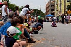 Zuschauer jubeln als Kinderrennen im Seifenkistenrennen zu Stockbilder