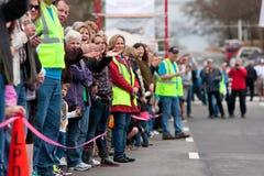 Zuschauer jubeln entgegenkommenden Teilnehmern an Kleinstadt-Rennen zu Stockfoto