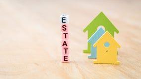 ZUSTANDS-Wort von Würfelbuchstaben hinter farbigen Haussymbolen auf Holzoberfläche Konzept Lizenzfreies Stockfoto