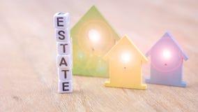 ZUSTANDS-Wort von Würfelbuchstaben hinter farbigen Haussymbolen mit Licht erweitert sich in den Fenstern auf Holzoberfläche Stockfoto