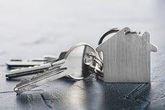 Zustandskonzept mit Schlüssel, keychain mit Haussymbol, Steinhintergrund Stockfotos