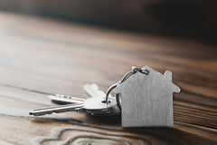 Zustandskonzept mit Symbol des Hauses, Schlüssel auf hölzernem Hintergrund Stockfoto