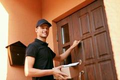 Zustelldienst Stattliche Arbeitskraft mit einem Kasten Kurier-With Package Near-Kunden-Tür lizenzfreie stockfotografie