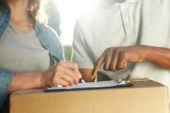 Zustelldienst Stattliche Arbeitskraft mit einem Kasten Schließen Sie herauf die Hände, die Dokumente unterzeichnen stockbilder