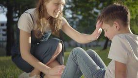 Zuster bindende schoenveters op de tennisschoenen van haar broer Het meisje dat om de kleine jongen geeft Relaties van siblings stock videobeelden