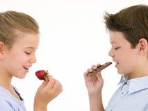 Zuster die aardbei eet door broer te eten Stock Fotografie