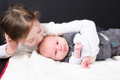 Zuster die zijn klein de peutermeisje van het broerkind en pasgeboren babyjongen in Concept gezinsleven kussen royalty-vrije stock foto