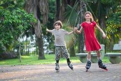 Zuster en broer die pret het rollerblading hebben Stock Fotografie