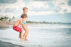Zuster en broer het spelen op het strand in de dagtijd Stock Afbeeldingen
