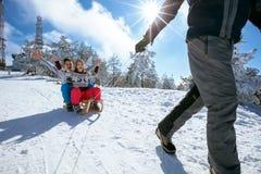Zuster en broer op sneeuw die en op de zonnige winter sledding genieten van Stock Foto