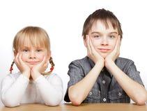 Zuster en broerzitting bij bureau royalty-vrije stock foto