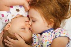 Zuster kussende baby Stock Afbeeldingen