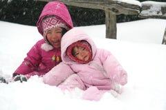 Zusters die in de sneeuw spelen royalty-vrije stock afbeeldingen