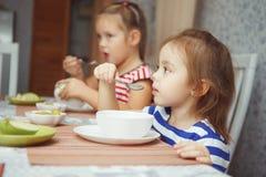Zusters die door lijst zitten en klaar om diner te eten royalty-vrije stock foto's