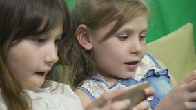 Zusters die in gadgets in bed thuis spelen stock video
