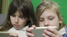 Zusters die in gadgets in bed thuis spelen stock videobeelden
