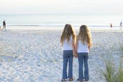 Zusters die handen op het strand houden stock foto