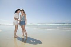 Zusters die shell op strand bekijken Stock Afbeeldingen