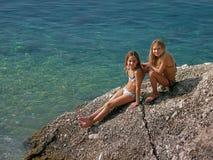 Zusters die (tweelingen) in de de zomervakantie genieten van stock foto