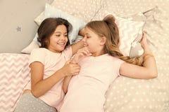 Zusters gelukkige kleine jonge geitjes die in slaapkamer ontspannen vriendschap van kleine meisjes Vrije tijd en pret Het hebben  royalty-vrije stock foto's