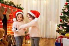 Zusterstweelingen in Kerstmanhoeden in een ruimte met het bekijken Kerstmis Stock Foto