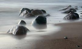 Zustrom einer Welle mit Steinen auf Sand Stockfotografie
