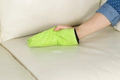 Zutreffen der Reinigungs-Lösung auf ledernes Sofa Lizenzfreie Stockbilder