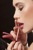 Zutreffen des Lipglosses auf die Lippen eines jungen Modells Lizenzfreies Stockfoto