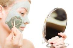 Zutreffen des transparenten Lacks Frau in der Lehmschlammmaske auf Gesicht schönheit Lizenzfreies Stockfoto