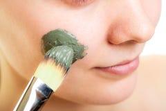 Zutreffen des transparenten Lacks Frau, die Lehmschlammmaske auf Gesicht anwendet Stockfoto