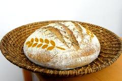 Zuurdesembrood met tarwekruid wordt verfraaid in een mand die royalty-vrije stock afbeelding