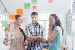 Zuverlässige junge Arbeitnehmer, die Anzeigen in einem modernen mit-arbeitenden Raum bekannt geben Stockbilder
