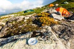 Zuverlässiger Kompass auf einem Stein in der Tundra nahe dem Zeltkampieren Das Konzept der Reise und des aktiven Lebensstils stockfoto