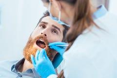 Zuverlässiger Zahnarzt, der sterile Instrumente beim Säubern des te verwendet stockbilder