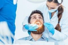 Zuverlässiger Zahnarzt, der sterile Instrumente beim Säubern des te verwendet stockfotos