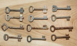 Zwölf symmetrisch vereinbarte Schlüssel auf einem hölzernen Hintergrund stockbild