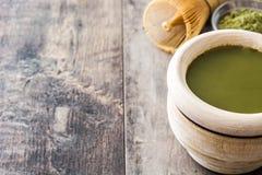 Zwaaien de Matcha groene thee in een kom en het bamboe, op hout Royalty-vrije Stock Afbeeldingen