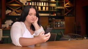 Zwaar Kaukasisch wijfje die haar telefoon jatten en in de koffie met grote document kop zitten stock footage