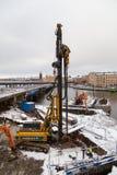 Zwaar materiaal die een stapel voor de bouw van stichtingen op een sneeuwdag door het water boren stock foto
