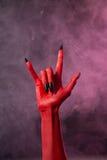 Zwaar metaal, rode duivelshand met zwarte spijkers Royalty-vrije Stock Afbeelding